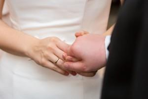 Frauenhand mit goldenem Ehering, Ausschnitt von Frau im Brautkleid und Mann im dunklen Anzug. Beide reichen sich die Hände zur Eheschließung.