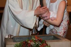 Arm von Priester und Mutter mit einem Baby, das getauft wird.