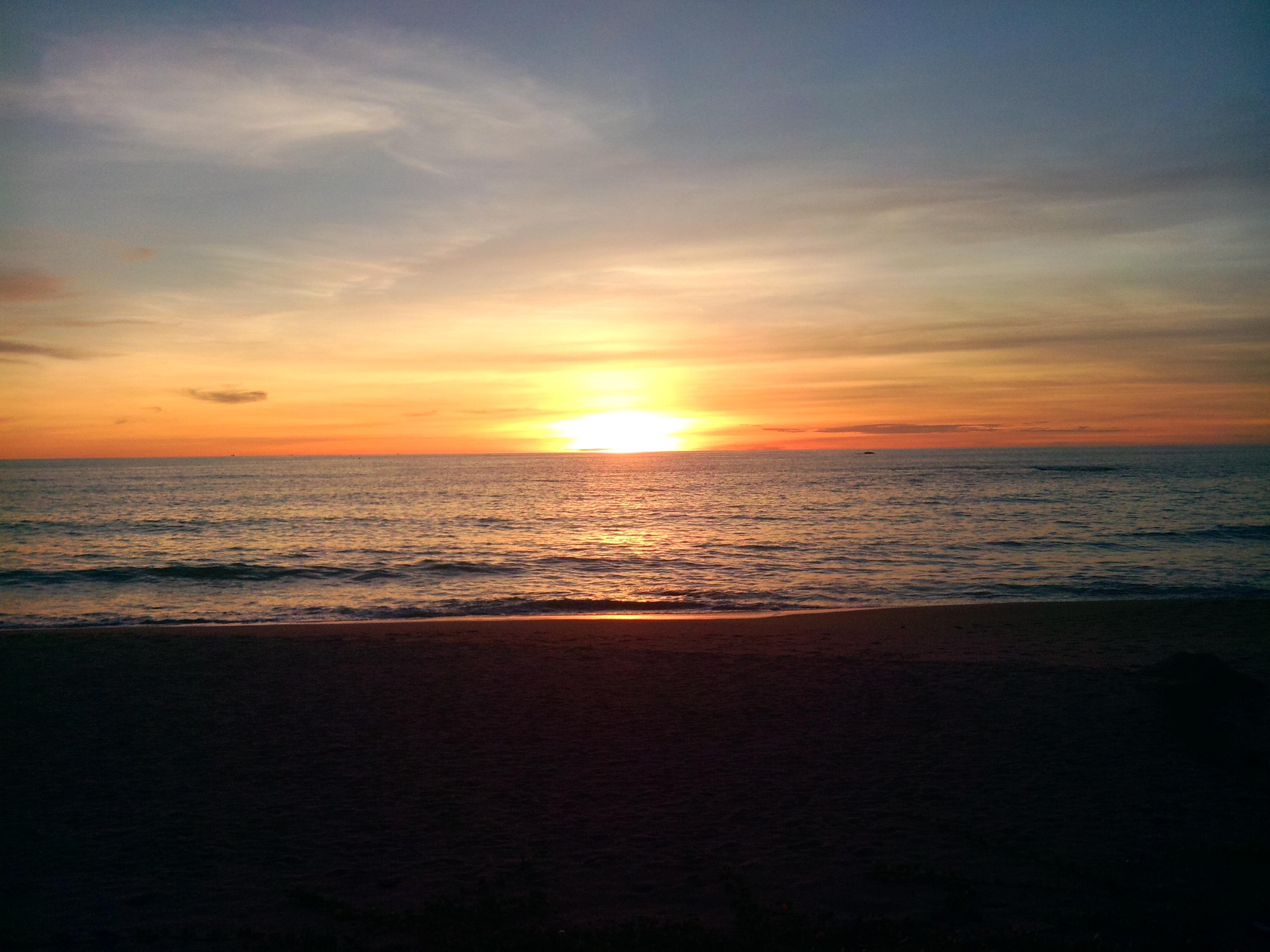 Strand mit Meer und roter untergehender Sonne