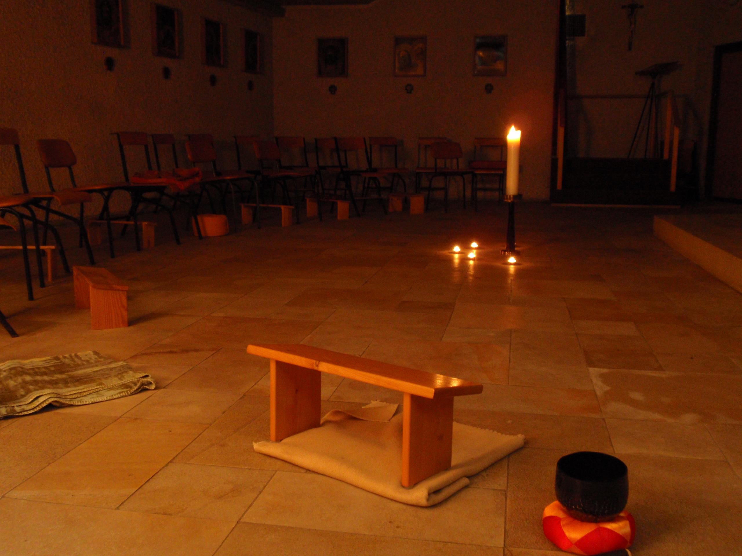 Gebetsschemel in einem schwach beleuchteten Raum mit Kerzen