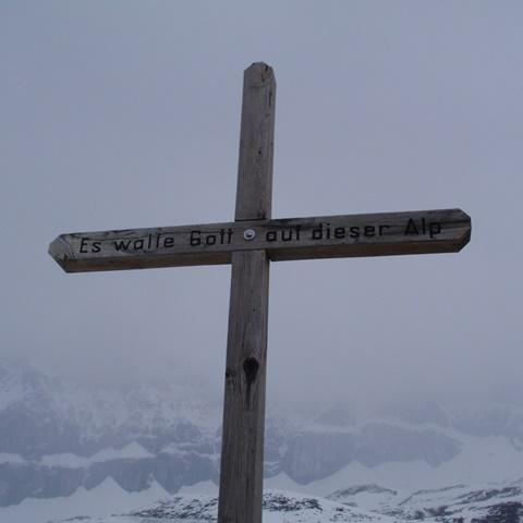 Kreuz auf Berggipfel vor Bergpanorama